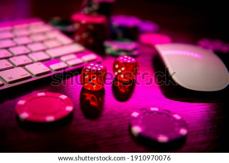 Online casino. Online poker. On the table there are game pieces and dice next to the keyboard. Game chips for betting in gambling. Dice. Poker chips. Royalty-Free Stock Photo #1910970076