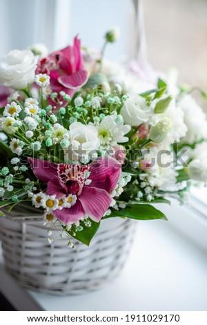 Delicate spring flower arrangement in a wicker basket. Flower arrangement for woman Royalty-Free Stock Photo #1911029170