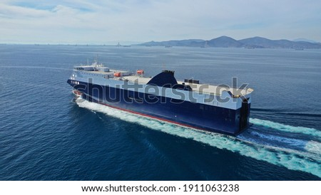 Aerial drone photo of Roll on Roll off vehicle carrier vessel (RO RO) cruising in Aegean deep blue sea, Greece Royalty-Free Stock Photo #1911063238