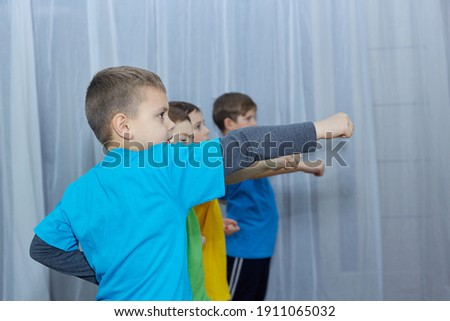 Boys athletes in multi-colored t-shirts hit a punch on a light background Royalty-Free Stock Photo #1911065032