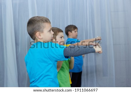 Boys athletes in multi-colored t-shirts make a punch on a light background Royalty-Free Stock Photo #1911066697