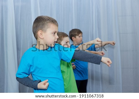 On a light background, boys athletes in colorful T-shirts perform a punch Royalty-Free Stock Photo #1911067318
