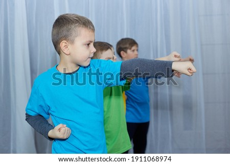 On a light background, boys athletes in colorful T-shirts make a punch Royalty-Free Stock Photo #1911068974