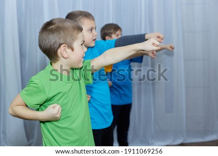 On a light background, boys in multicolored T-shirts hit a punch Royalty-Free Stock Photo #1911069256