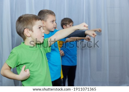 On a light background, boys athletes in multi-colored T-shirts are training a punch Royalty-Free Stock Photo #1911071365