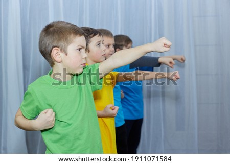 On a light background, boys in multi-colored T-shirts practice a punch Royalty-Free Stock Photo #1911071584
