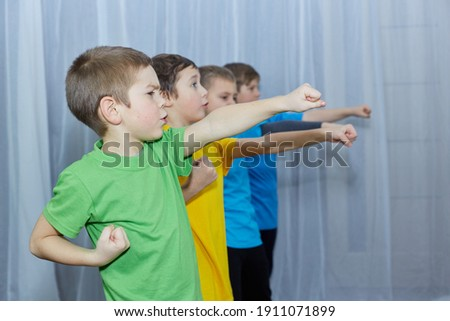 On a light background, boys in multi-colored T-shirts make a punch Royalty-Free Stock Photo #1911071899