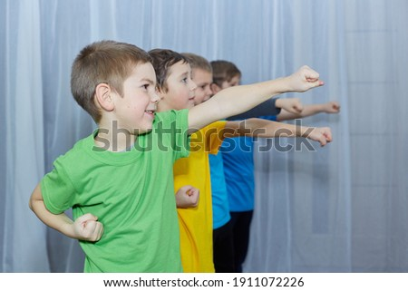 On a light background, boys in multicolored T-shirts hit a punch Royalty-Free Stock Photo #1911072226