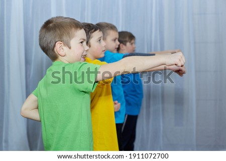 On a light background, boys in colorful T-shirts perform a punch Royalty-Free Stock Photo #1911072700