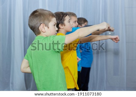 Boys in multicolored t-shirts perform a punch on a light background Royalty-Free Stock Photo #1911073180