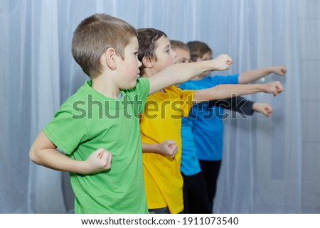 Boys in multicolored t-shirts make a punch on a light background Royalty-Free Stock Photo #1911073540