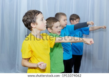 Boys in multicolored t-shirts beat a punch on a light background Royalty-Free Stock Photo #1911074062