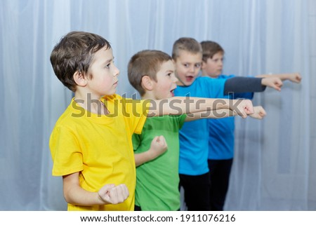 Boys in multicolored T-shirts perform a punch Royalty-Free Stock Photo #1911076216