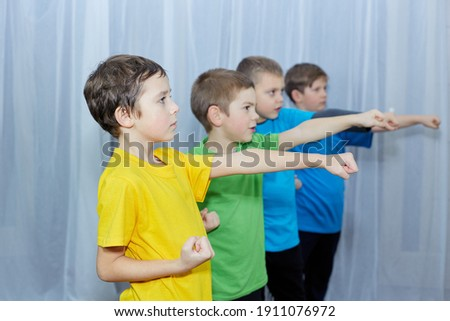 Boys in colorful T-shirts hit the punch Royalty-Free Stock Photo #1911076972