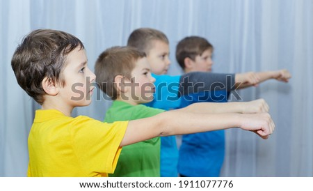 Boys in colorful T-shirts practice punching Royalty-Free Stock Photo #1911077776