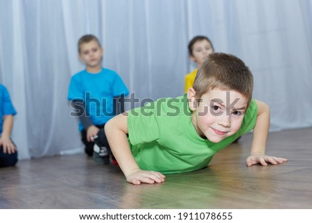 Little athlete in a green T-shirt stands in the support lying on a light background Royalty-Free Stock Photo #1911078655