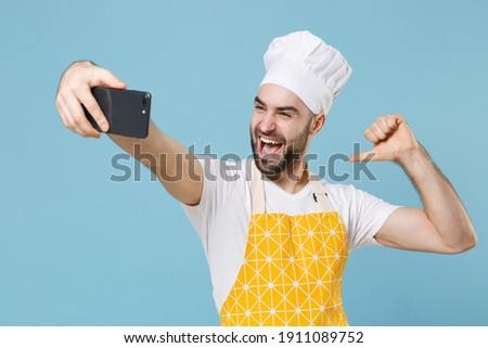 Excited young bearded male chef or cook baker man in apron white t-shirt toque chefs hat isolated on blue background. Cooking food concept. Doing selfie shot on mobile phone pointing thumb on himself