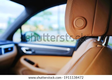 Close up of modern luxury brown car leather passenger seat with blurred sedan interior components and window view of outside. Vehicle industry design element. Detail of leather auto headrest texture. Royalty-Free Stock Photo #1911138472