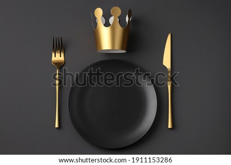 Festive creative royal table setting on a dark background. Gold crown, fork and knife. Valentine's Day, Wedding Day, Birthday, Women's Day and Mother's Day. Flat lay Royalty-Free Stock Photo #1911153286