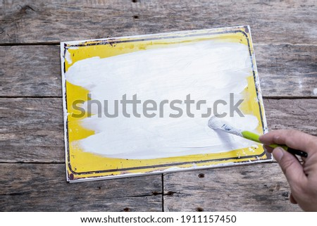 hand white painting a sign