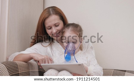 Treat your child for colds at home. Mom treats her daughter with inhalation and together they watch cartoons on tablet. Child is receiving respiratory therapy with nebulizer. Child suffers from cough.