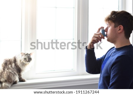 Young man using puffer inhaler to control his asthma caused by pet allergies Royalty-Free Stock Photo #1911267244