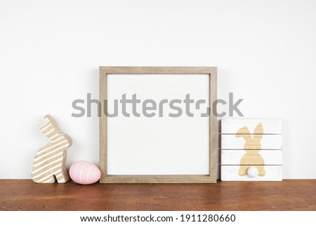 Mock up wood frame with Easter decor on a wood shelf. Shabby chic wood sign, egg, bunny. Square frame against a white wall. Copy space.