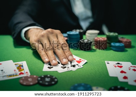 Man dealer or croupier shuffles poker cards in a casino on the background of a table, poker game concept Royalty-Free Stock Photo #1911295723