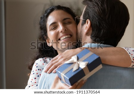 Happy birthday, my love. Rear view of tender young husband greeting touched wife with important date. Grateful millennial woman embracing with warmth beloved man holding gift box with present surprise