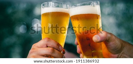Close-up view of a two glass of beer in hand. Beer glasses clinking at outdoor bar or pub Royalty-Free Stock Photo #1911386932