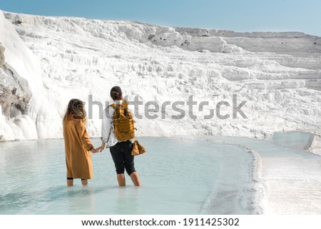 Couple of lovers standing, holding hands and taking selfie, pictures in geothermal pool surrounded by travertines, white mountains of salt in Pamukkale, Turkey. Turkey national, natural landmarks