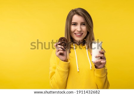 Photo of attractive lady poses in a cute way with glass of milk and cookie. Wears casual yellow hoody, isolated yellow color background