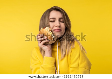 Photo of attractive lady poses in a cute way with burger. Wears casual yellow hoody, isolated yellow color background