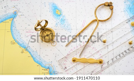 """Retro styled golden compass (sundial), antique vintage W HC 6"""" brass dividers calipers nautical navigation chart tool, parallel ruler, old white map close-up. Vintage still life. Sailing accessories Royalty-Free Stock Photo #1911470110"""