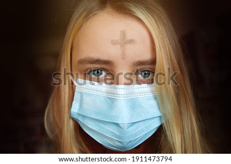 Girl with cross made from ash on forehead with face mask. Ash wednesday concept.