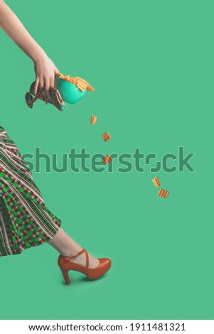 a woman walks into the picture with a bowl filled with chips and red seventies-style high heels