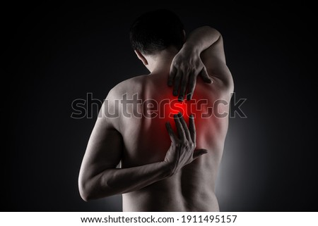 Pain between the shoulder blades, man suffering from backache on black background, painful area highlighted in red Royalty-Free Stock Photo #1911495157