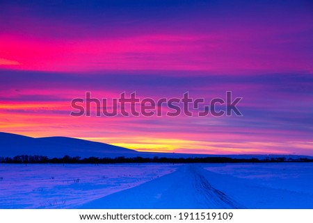 Winter road with mountain during amazing vivid saturated beautiful sunset sky in pink, purple and blue colors. Sunset background Royalty-Free Stock Photo #1911519109