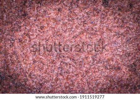 Dark red granite background, structured background with vignetting, darkening around the edges of the photo. Natural stone texture.