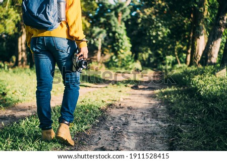 unrecognizable man with backpack and boots holding a camera in front of a path in a forest, nature travel and hiking concept.