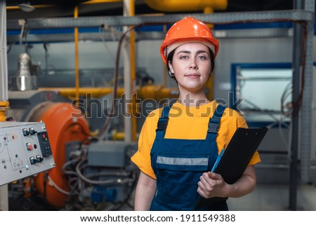Industrial production. Portrait of a young Caucasian woman in uniform and helmet with a folder in her hand. In the background, boiler equipment. The concept of gender equality. Royalty-Free Stock Photo #1911549388