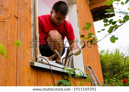 Replacement of a window and a window frame, dismantling of an old window in a private house in the countryside, the worker dismantles an old wooden window.2020 Royalty-Free Stock Photo #1911569392