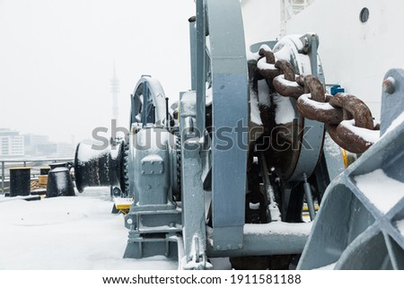 The mooring deck of a cargo ship with anchor winches, an anchor chain on winches, bollards and haws with mooring ropes, frozen and covered in snow. Snow on the mooring deck of a cargo ship. Royalty-Free Stock Photo #1911581188