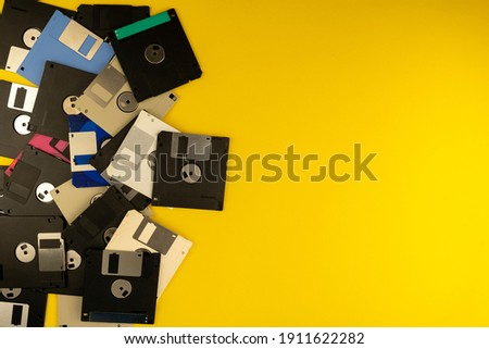 Floppy disk 3.5 inch. The diskettes 3 2 are a technology icons of de decade of 80s. Retro, vintage and colourful computer diskette. Yellow background. Copy space.
