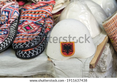 Traditional Ottoman market in Kruja, birth town of National Hero Skanderbeg. Flea market in Albania. Wool craft souvenirs for sale. Traditional Albanian male headdress on foreground. Royalty-Free Stock Photo #1911637438