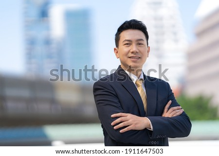 Portrait of successful asian businessman standing with arms crossed standing in front of modern office buildings Royalty-Free Stock Photo #1911647503