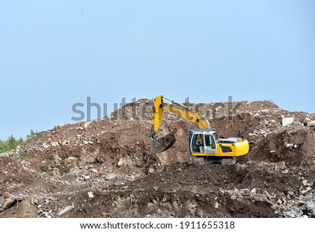 Recycling concrete and construction waste from demolition. Excavator at landfill of the disposa. Reuse of building rubble. Backhoe dig gravel at mining quarry. Concrete debris  Royalty-Free Stock Photo #1911655318