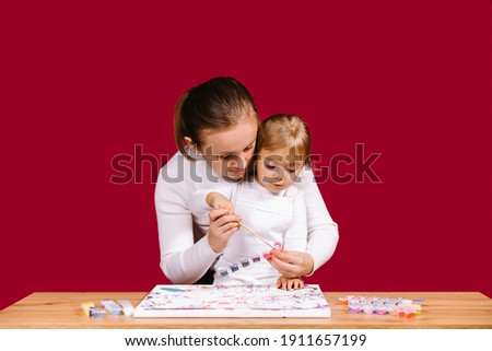 Home family activity. Mom help little daughter to paint with brush and acrylic kit a picture on numbers. Curious blonde little girl is excited of workshop