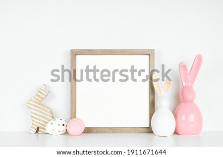 Mock up wood frame with Easter egg and bunny decor on a white shelf. Square frame against a white wall. Copy space.