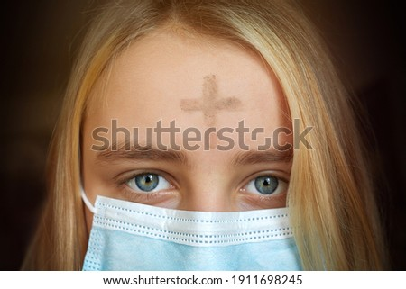 Girl with cross made from ash on forehead with face mask. Ash wednesday concept. Royalty-Free Stock Photo #1911698245